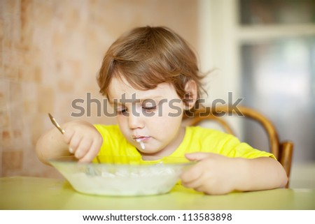 2 years child himself eats from plate with spoon - stock photo