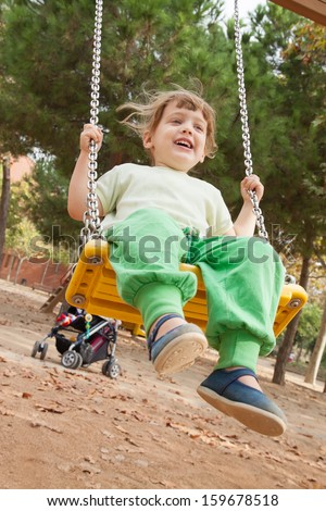 3 years child on swing against urban  landscape - stock photo