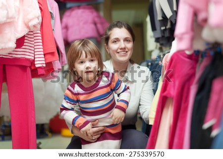 2 years child with mother chooses wear at clothes shop. Focus on girl - stock photo