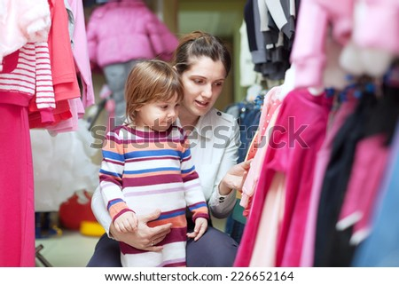 2 years child with mother chooses wear at clothes store - stock photo