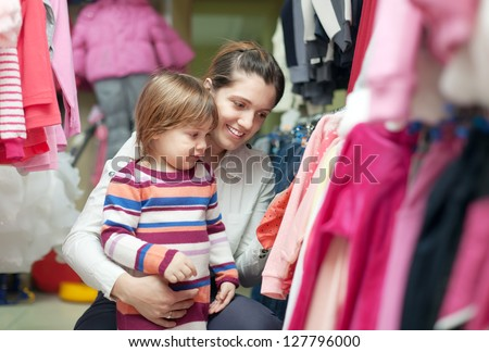 2 years child with mother chooses wear at shop - stock photo