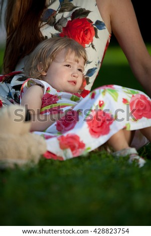 2 years girl resting on the grass with her mother - stock photo
