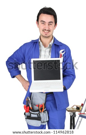 30 years old artisan showing a laptop in a room full of tools - stock photo