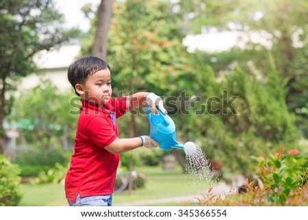 5 years old asian boy in his flower garden - kids and family. Portrait of a boy working in the garden in holiday - stock photo