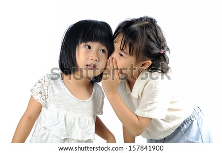 5 years old asian girl whispering to her younger sister isolated in white background