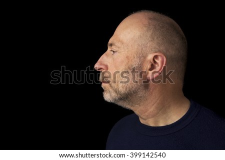 60 years old  bald man with a beard - a profile headshot against a black background
