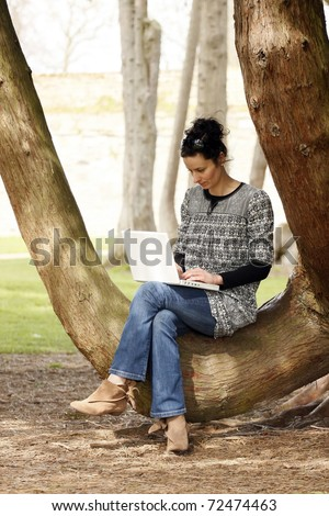 30-35 years old beautiful woman portrait working on laptop computer natural in park - stock photo