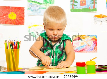 2 years old blond boy drawing with pencil on preschool art class with images on background - stock photo