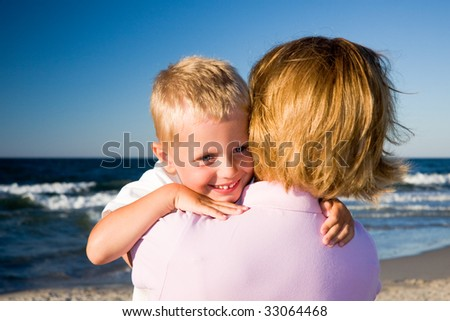 3 years old boy hugging his mother on a beach in sunny day - stock photo