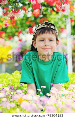 9 years old boy in his flower garden - kids and family - stock photo