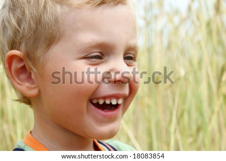 3 years old boy laughing on a wheat field