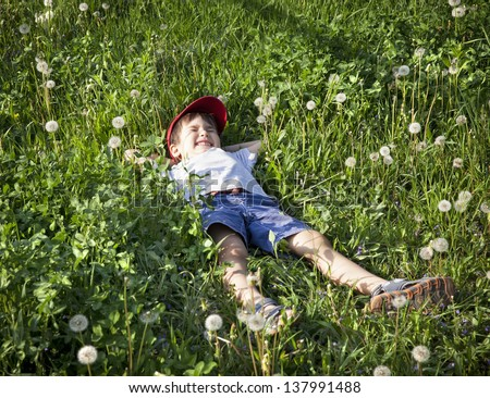 4 years old boy lying on the grass - stock photo