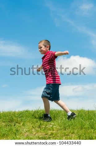 6 years old boy running with arms extended very happy in a park during summertime - stock photo