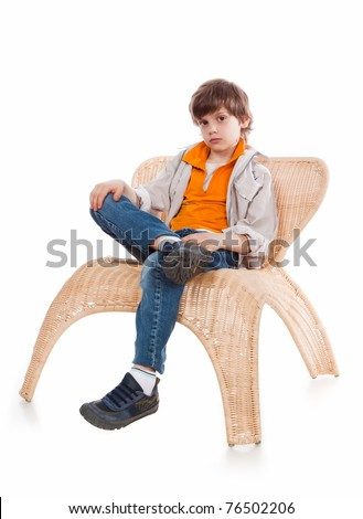 7 years old boy sitting on a wicker chair on a white background