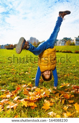 10 years old boy standing on hands outside on sunny day balancing  - stock photo