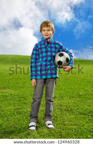 7 years old boy standing on the field with football ball