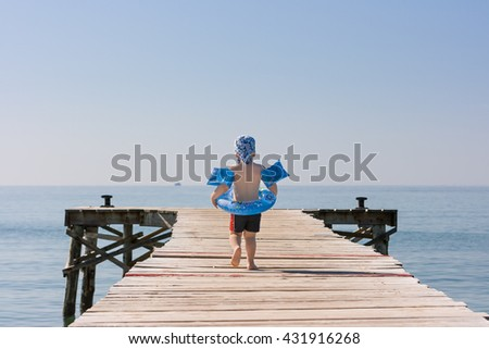 3 years old boy walking on beach wooden pier ready to swim in a sea. Summer outdoor activities with children on the beach. Blue sky and ocean in the morning. Safety first. - stock photo