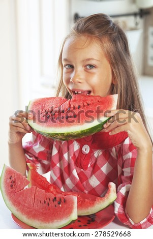 8 years old child eating watermelon at home
