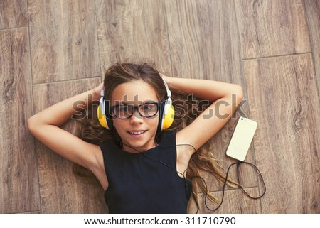 9 years old child is lying down on the floor and listening to music, top view point - stock photo