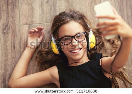9 years old child is lying down on the floor, listening to music and taking selfie, top view point - stock photo