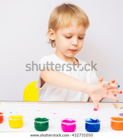 4 years old child painted with hands. Exciting baby boy playing with paint isolated on white background. Boy wearing white t-shirt. Kid sitting at table making colorful hand prints on paper. - stock photo
