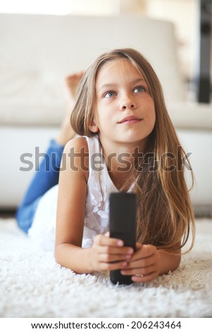 8 years old child watching tv laying down on a white carpet at home alone - stock photo