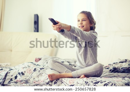 8 years old child watching tv, relaxed in parent's bed in morning at home - stock photo