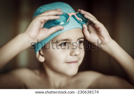 5 years old child with cap and goggles ready to swim - stock photo
