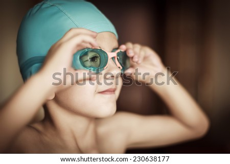 5 years old child with cap and goggles ready to swim