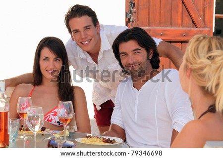 30 years old couple and a 20 years old man behind them posing outside at lunch time, summer scene - stock photo