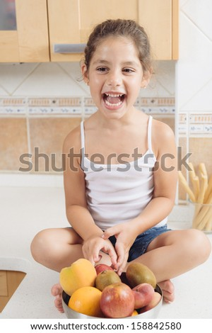 4 years old girl having healthy breakfast. She is funny and crazy. - stock photo