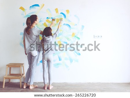8 years old girl painting the wall at home, Instagram style toning - stock photo
