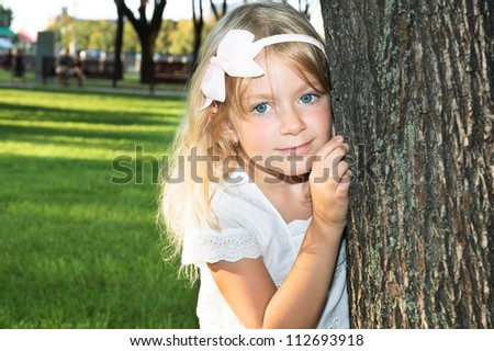 6 years old girl playing at park behind a tree - stock photo