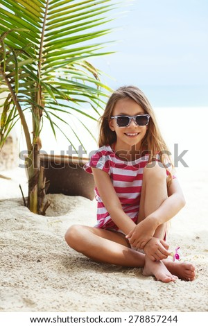 8 years old girl resting on the tropical palm beach in Thailand in summer - stock photo