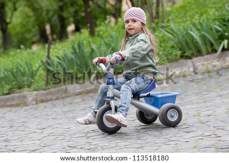 4 years old girl wearing jeans, pink cap and green coat rides on tricycle - stock photo