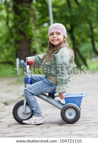 4 years old girl wearing jeans, pink cap and green coat sitting on tricycle and smiling - stock photo