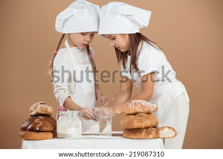 5 years old girls cooking together, studio shot - stock photo