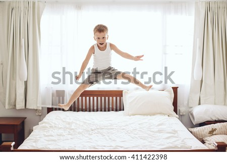6 years old little boy is jumping on the parent's bed - stock photo