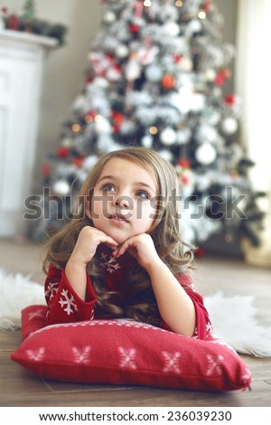 5 years old little girl laying down on soft cushion and looking up near Christmas tree at home - stock photo