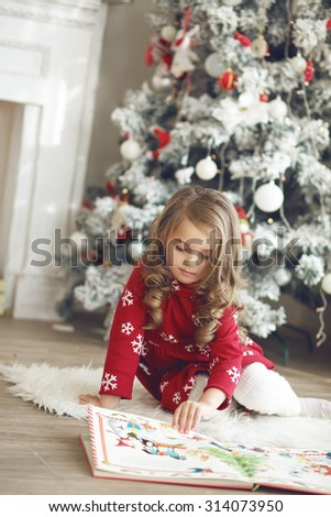 5 years old little girl reading book with winter tales from Santa Claus near Christmas tree in morning at home - stock photo