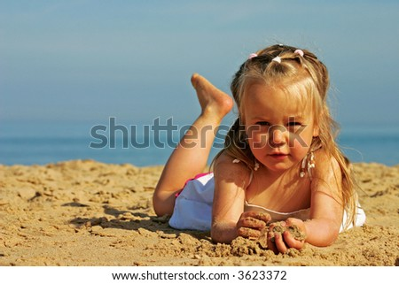 3 years old little girl relaxing and playing with sand on a beach