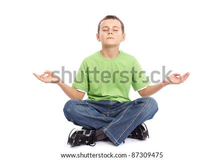 10 years old schoolboy meditating isolated on white