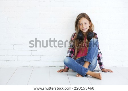 8-9 years old stylish teen girl with black headphones posing on white background - stock photo