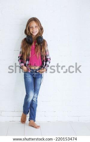 8-9 years old stylish teen girl with black headphones posing on white background - stock photo