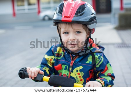 2 years old toddler boy in helmet learning to ride on his first bike - stock photo