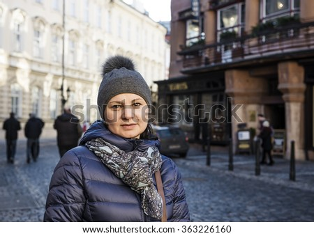 30-35 years old woman in autumn coat walks through the city - stock photo