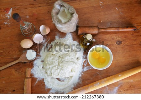yeast dough, eggs  and flour on wooden background