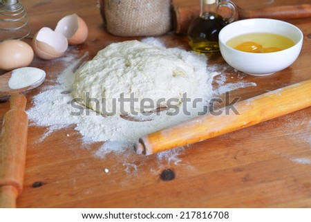 yeast dough, eggs  and flour on wooden background - stock photo