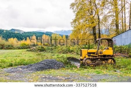 yellow small loader tractor in  autumn season - stock photo