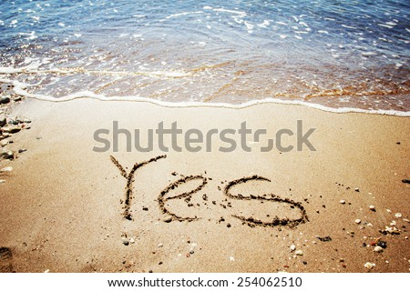 """""""Yes"""" written in the sand on sea background - stock photo"""